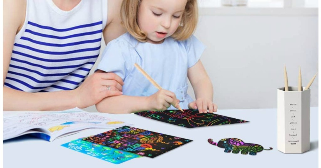 little girl playing with Scratch Art Set