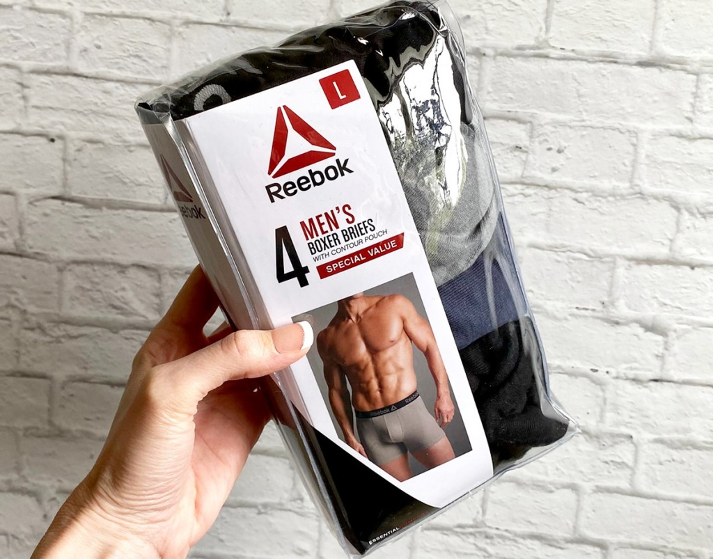 woman holding up a package of men's reebok boxer briefs against white brick wall