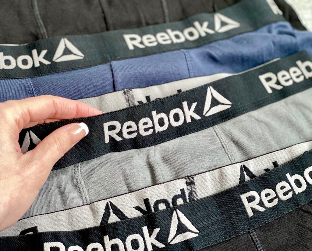woman holding up a grey and black pair of reebok brand boxer briefs in with multiple colors of pairs behind it