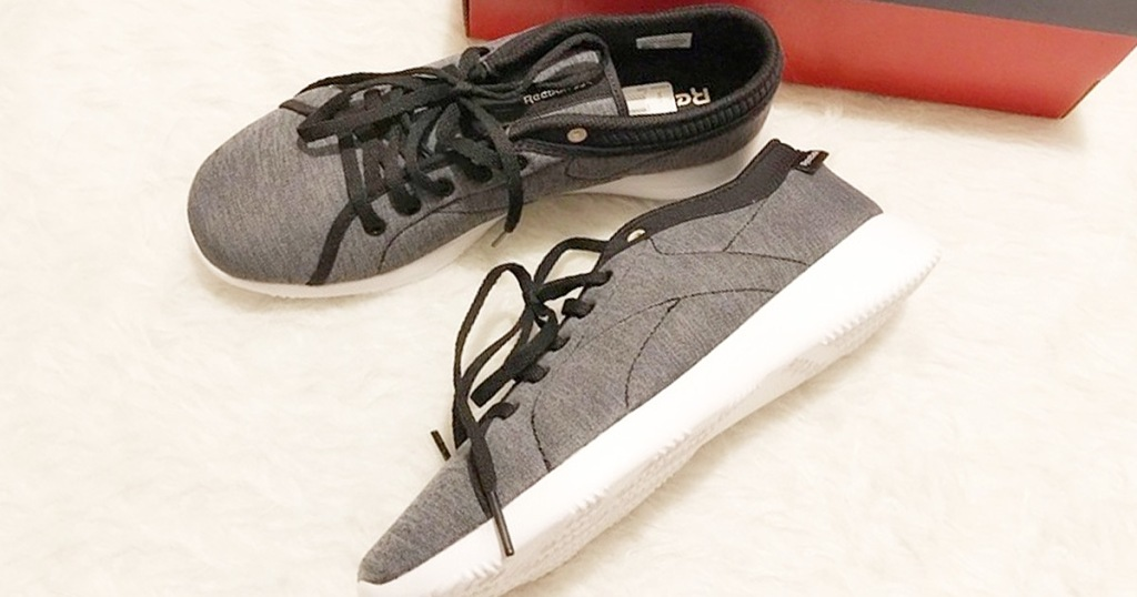 black and grey fabric reebok shoes on white fluffy rug