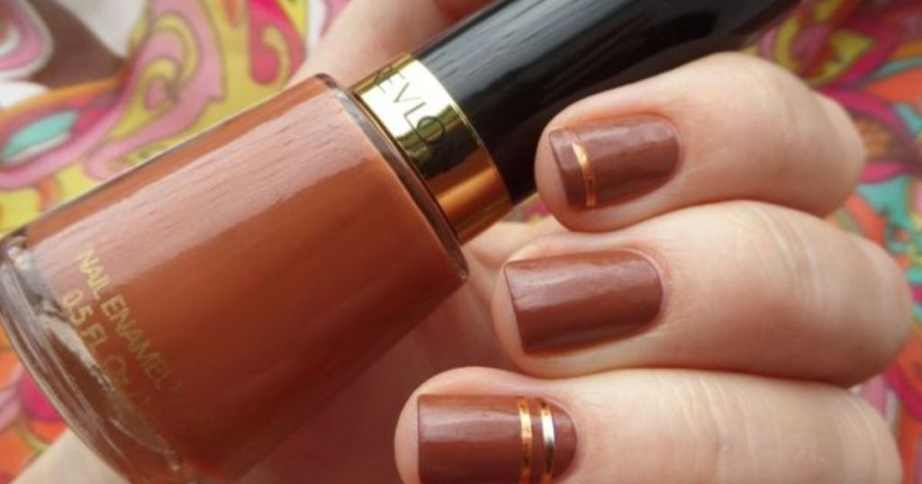 hand holding bottle of nail polish with painted fingernails