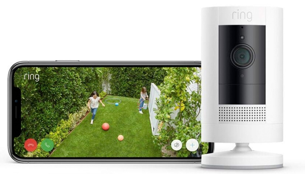 white ring security camera next to smartphone showing footage of kids playing in yard