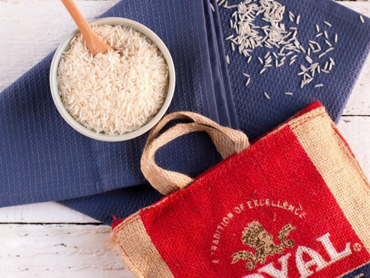 Large bag of rice with handles near small bowl of rice on white wooden surface