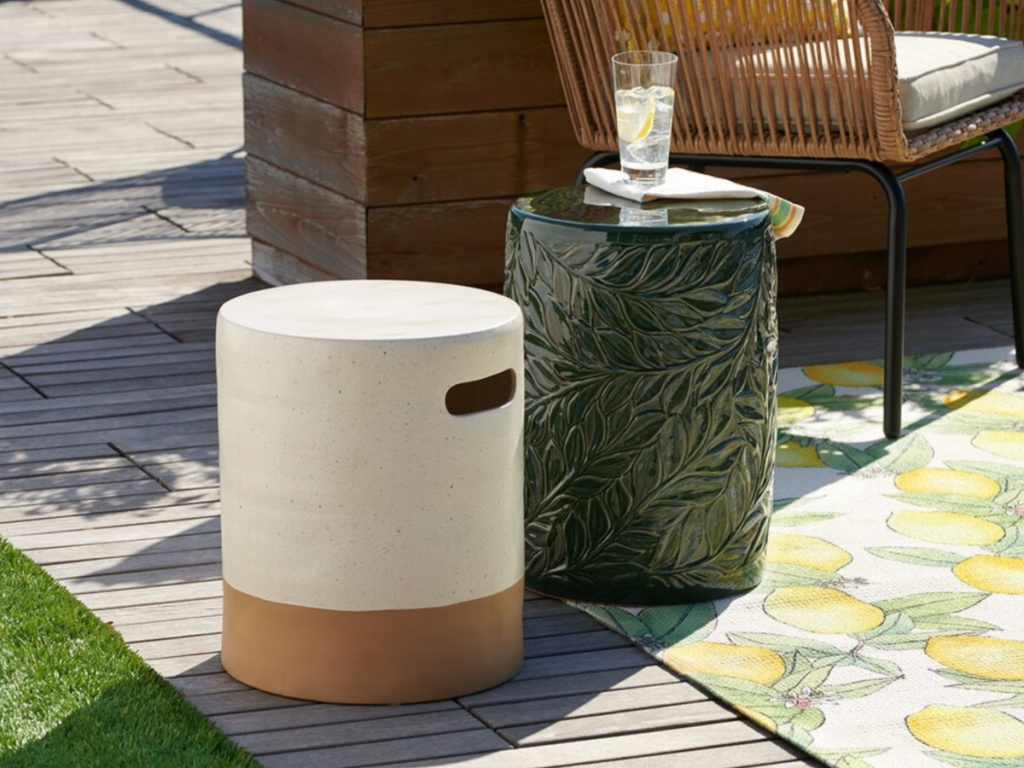 white and tan ceramic drum table and green leaf drum table outside