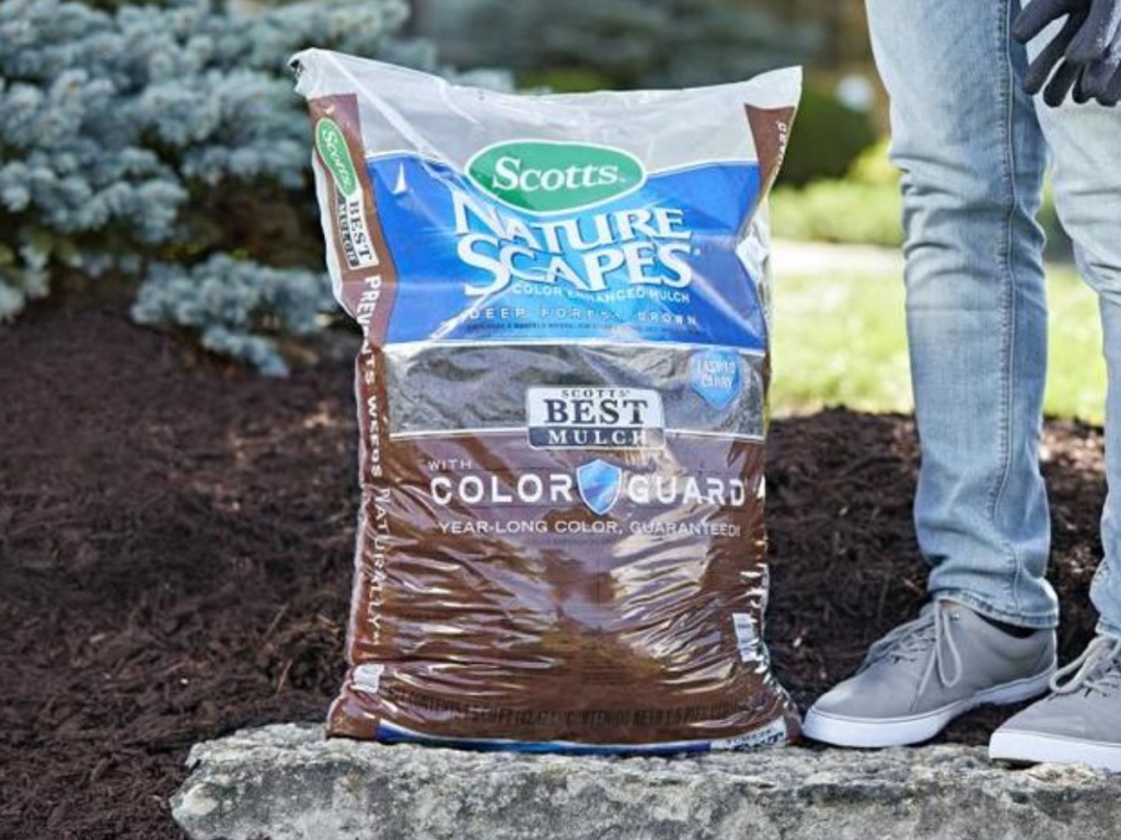 person standing next to large bag of brown mulch on rock in garden