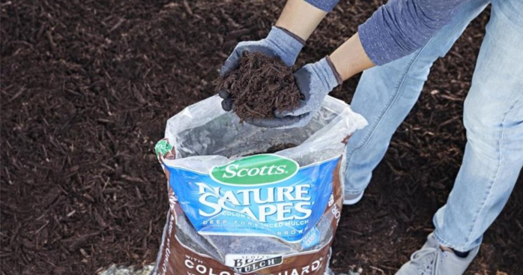 person with gloved hands holding brown mulch from large bag of mulch outside