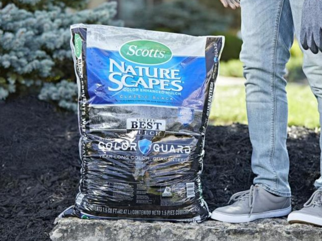 person standing next to large bag of black mulch on rock in garden