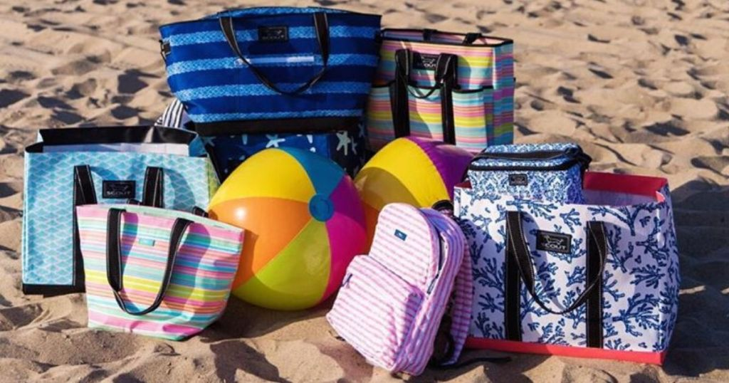 a bunch of tote bags on the beach with a beach ball