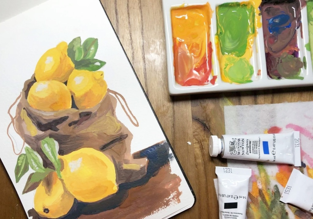 acrylic painting of lemons in brown bag on table next to paint in tray and paint tubes