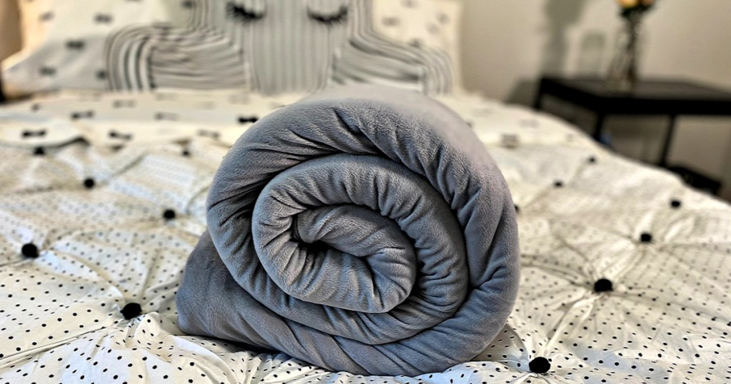 Sleep Mantra Weighted Blanket rolled up on bed