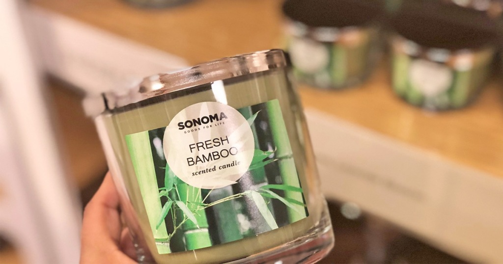 person holding up a green fresh bamboo scented candle in front of store display