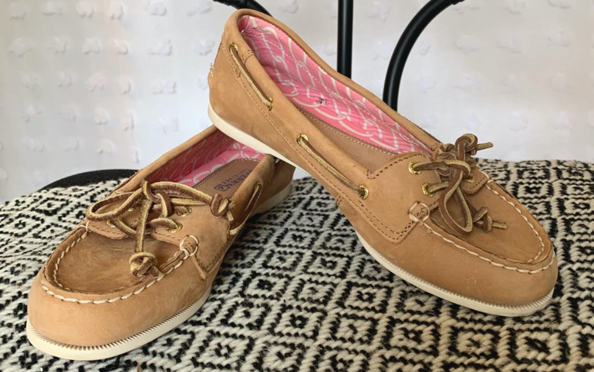 women's tan boat shoes on table