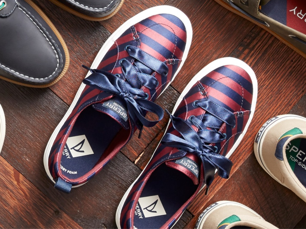 red and blue striped satin sneakers on wooden surface with other shoes
