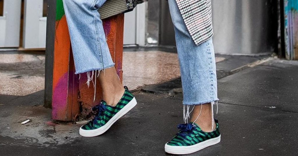 woman on street in jeans and green and blue striped satin sneakers