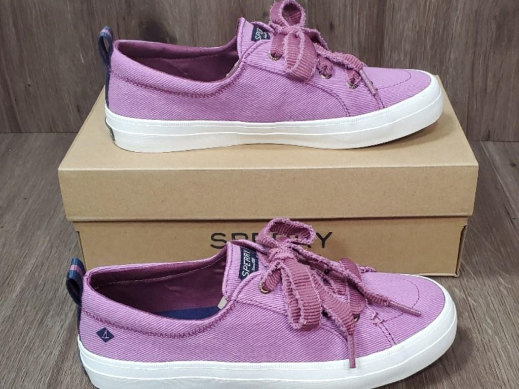 pink women's sneakers on shoe box