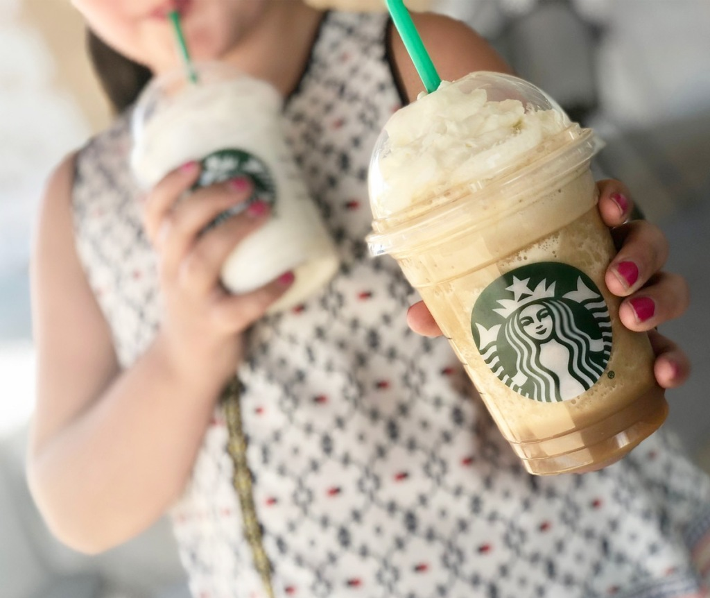 girl with two starbucks frappuccinos, drinking one while holding other out to camera