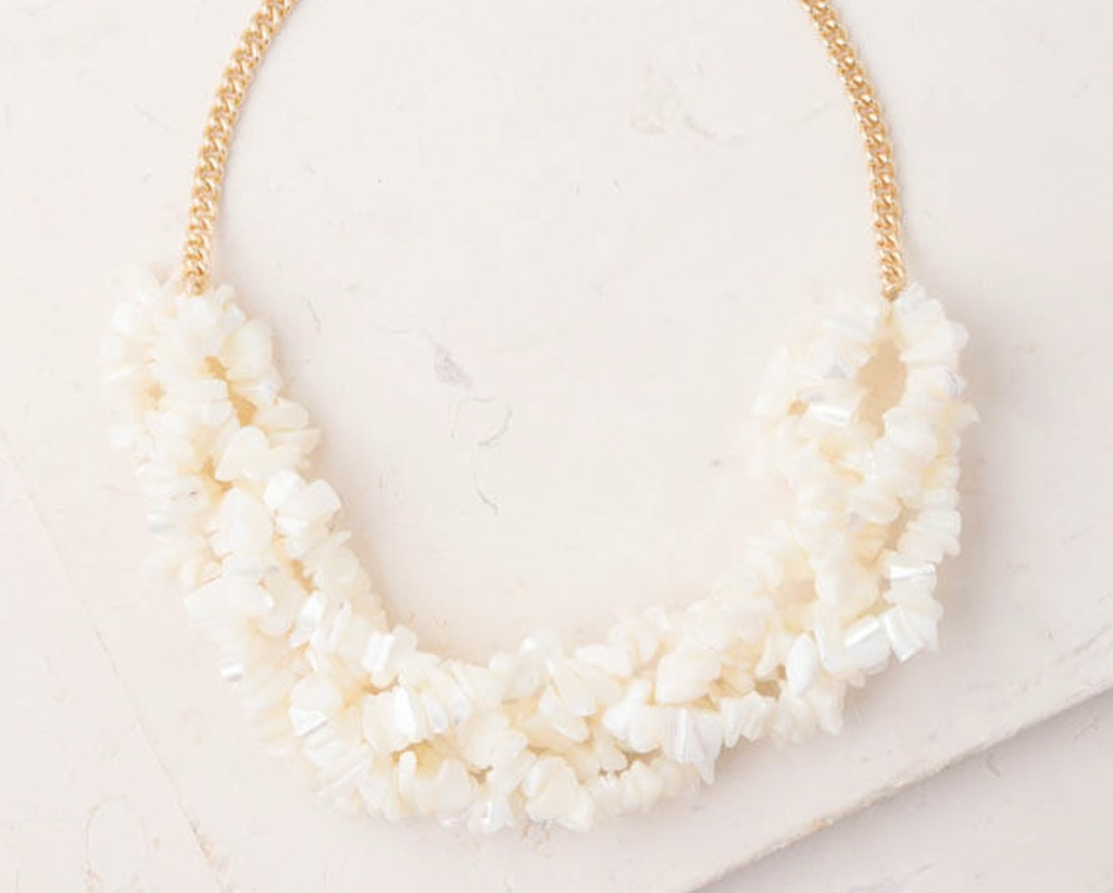 gold and white statement necklace made from beaded pieces of pearl