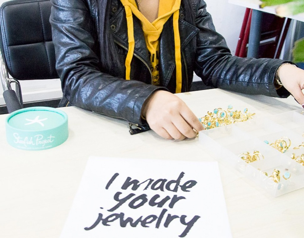 woman hand making pairs of earrings with sign saying she makes your jewelry