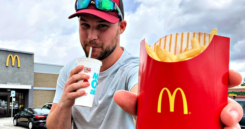 man holding McDonald's Fries and drink in Mcdonald's parking lot