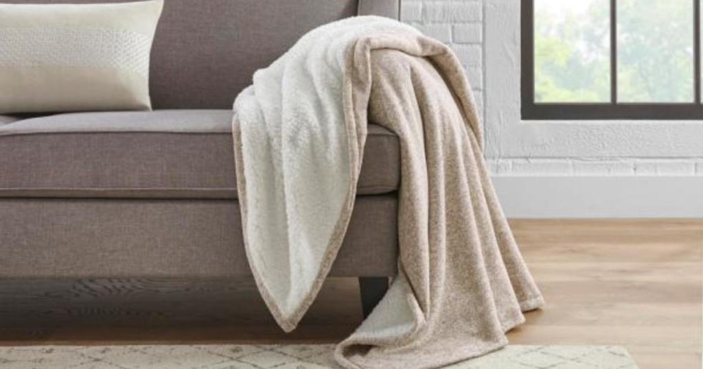 Khaki colored StyleWell Oversized Sweater Knit Sherpa Blanket drapped over couch in living room