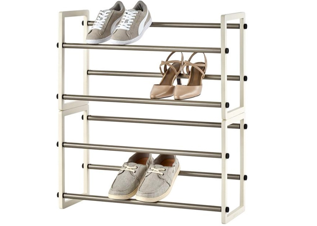 white shoe rack with four levels and three pairs of shoes on it