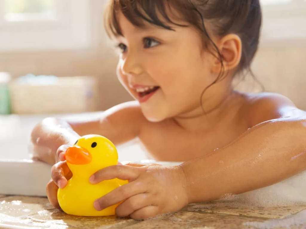 little girl taking a bath and holding a yellow rubber ducky