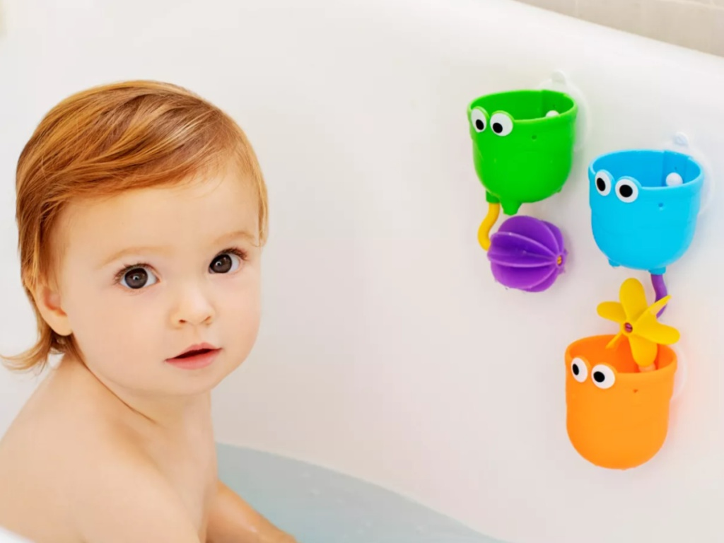 baby girl sitting in a bath tub with bath toys attached to the side of the tub