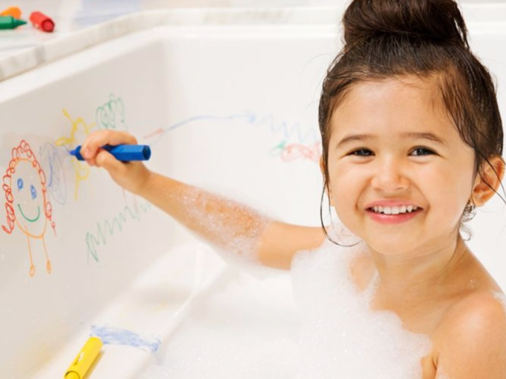 little girl sitting in a bath tub drawing on the side