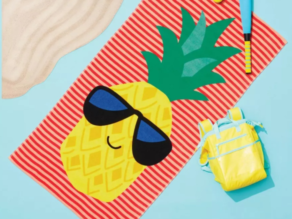 Target Pineapple Beach Towel on a blue background with a backbpack and fake sand