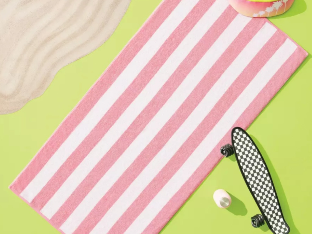 pink and white striped beach towel on green background with fake sand and a skate board