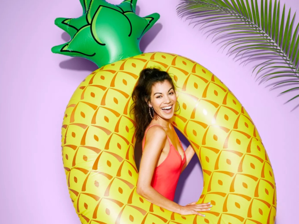 woman wearing a bright swimsuit holding a giant pineapple pool float