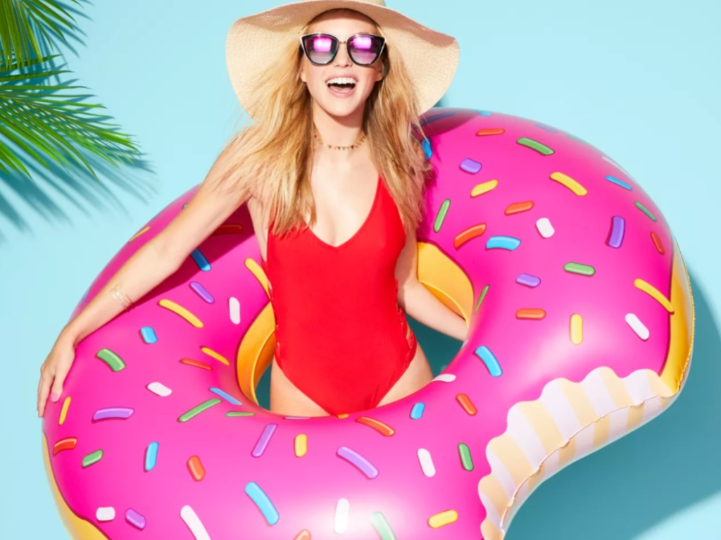woman wearing a red swimsuit holding a large donut shaped pool float