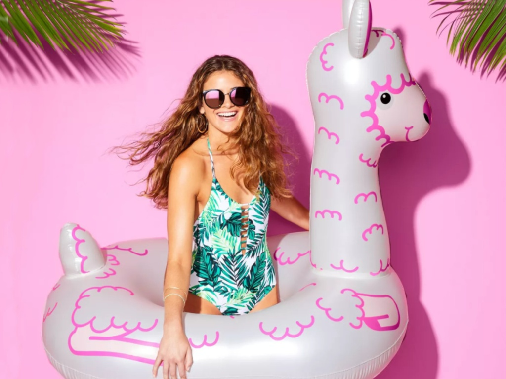 woman wearing a swimsuit holding a large white and pink colored llama pool float