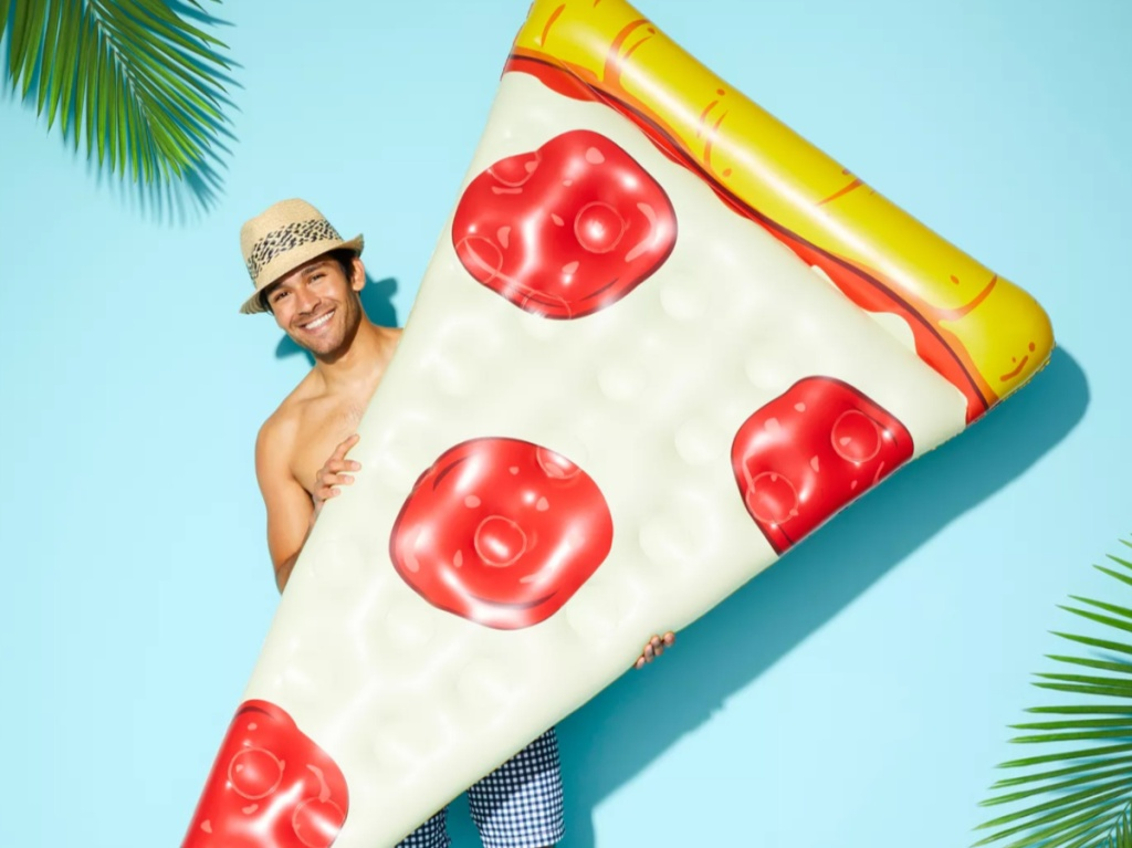 man wearing a hat and swim trunks holding a large pizza pool float