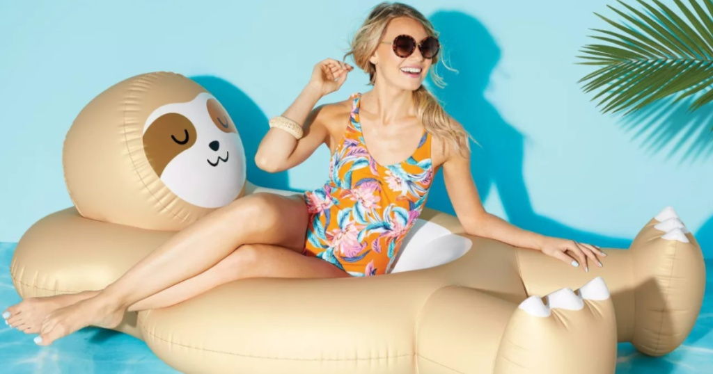 woman sitting on a large inflatable sloth pool floatie wearing a swimsuit and sunglasses