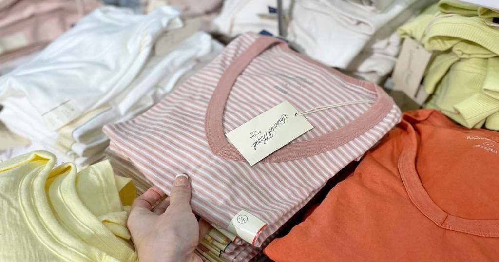 woman holding a pink and white striped t-shirt at a store display of shirts