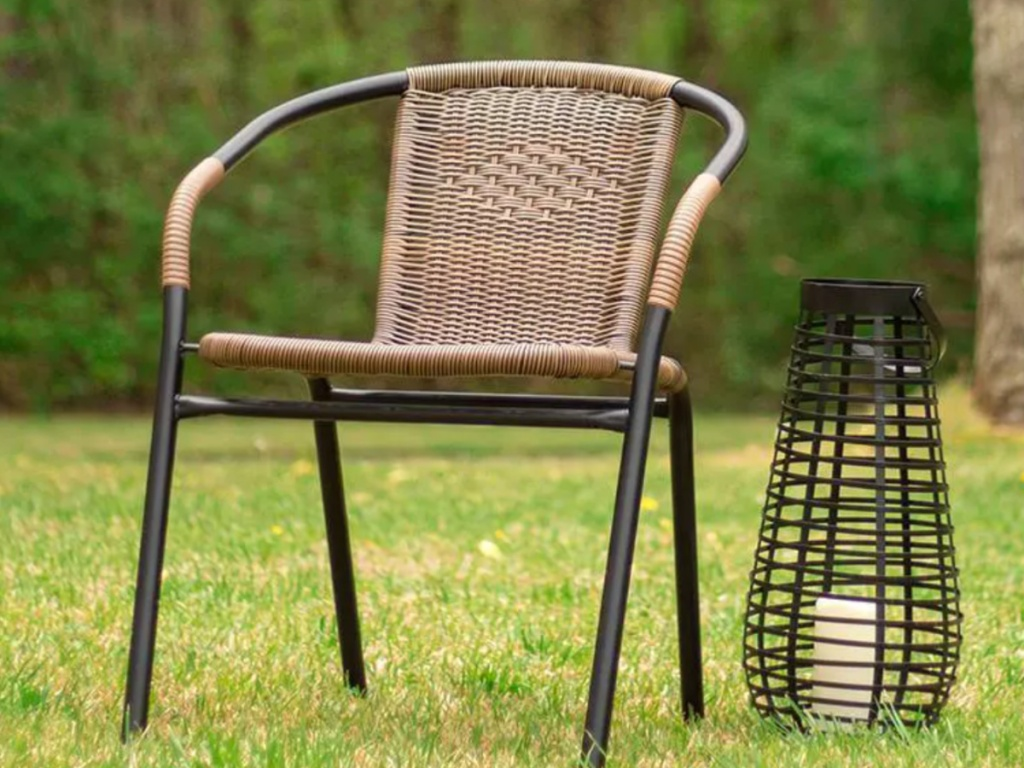 black and brown rattan lawn chair sitting on the grass next to a black lantern