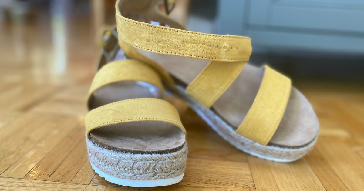 Women's strappy sandals in yellow color with white soles on wooden surface