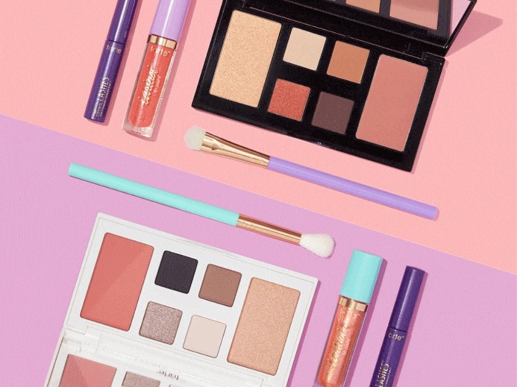 two makeup palettes, lipsticks, mascara, and brushes on pink and purple background