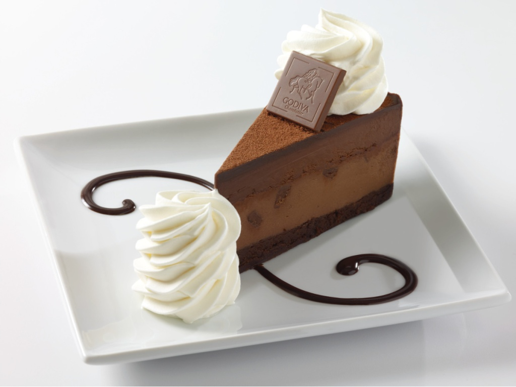 white plate with chocolate sauce design and whipped cream with slice of Godiva Chocolate Cheesecake