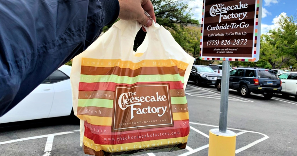 The Cheesecake Factory togo bag in person's hand