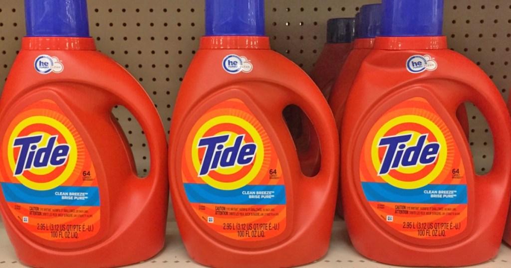 three orange bottles of tide laundry detergent on store shelf