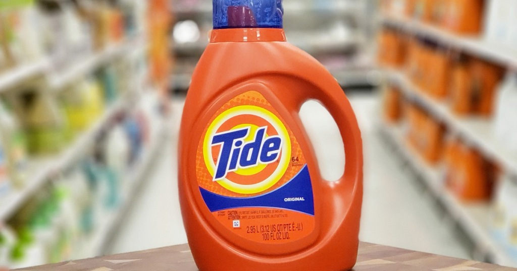orange bottle of tide laundry detergent on wooden shelf looking down laundry care aisle of store