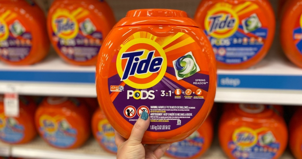 manicured hand holding tub of laundry detergent pacs in laundry aisle in store