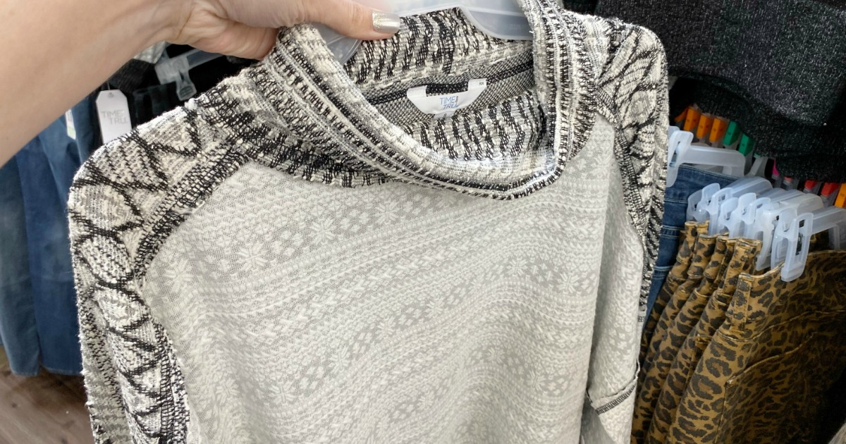 hand holding a sweater on a hanger
