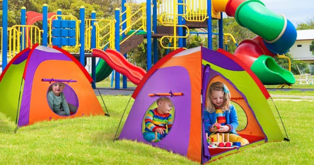 children in two colorful tents in grass by playground
