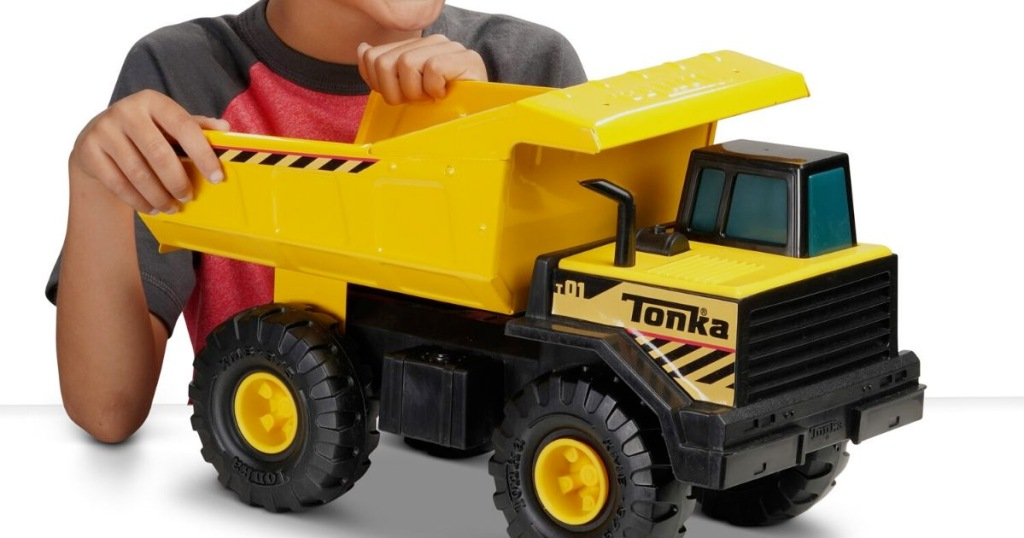 boy playing with yellow and black tonka dump truck