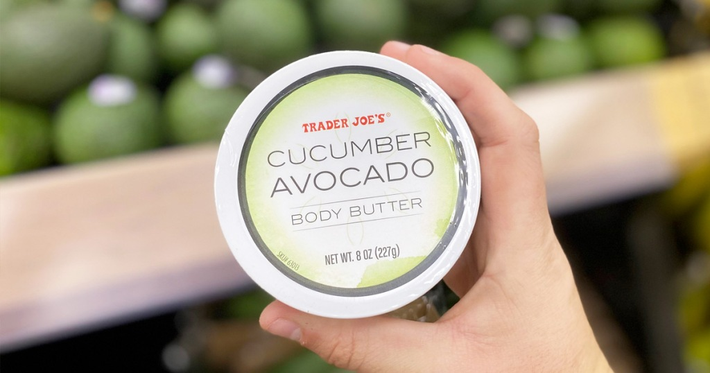 person holding a round container of Trader Joe's Cucumber Avocado Body Butter near avocado display in store