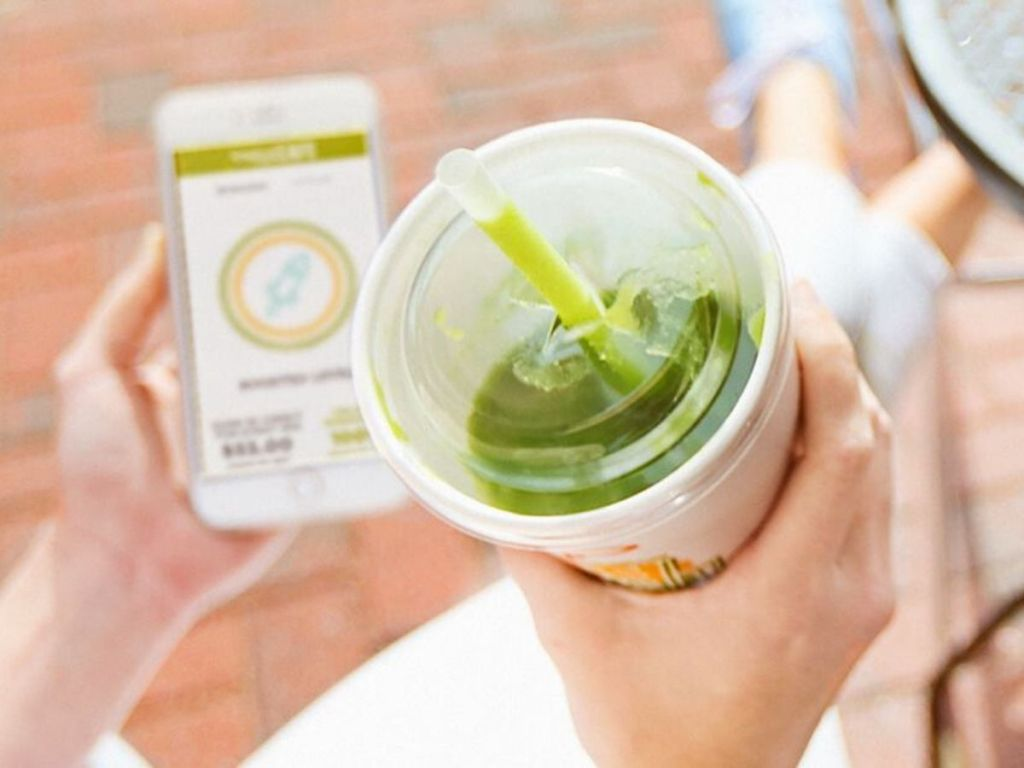 woman holding phone in one hand and smoothie in the other