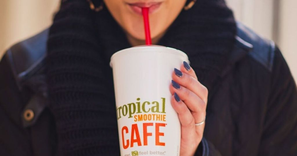 woman drinking a smoothie from a disposable cup with a straw